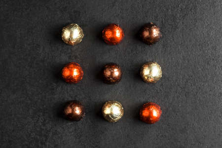 Chocolate candies wrapped in multicolored foil on dark background. Flat lay, top view 版權商用圖片