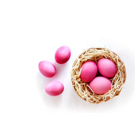 Easter composition with wicker nest and pink colored eggs on white background. Top view, copy space