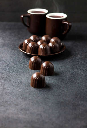 Chocolate candies on a plate and two cups of hot coffee on dark background with copy space 版權商用圖片