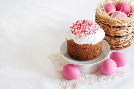 Minimalistic Easter composition with wicker basket with pink colored eggs and Easter cake on white background. Copy space 版權商用圖片