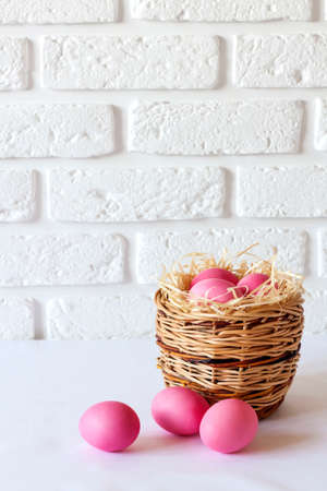 Minimalistic Easter composition with wicker basket and pink colored eggs on white background. 版權商用圖片
