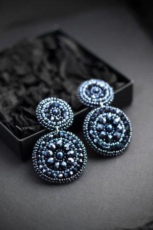Deep blue seed beads embroidered statement earrings on black background 版權商用圖片