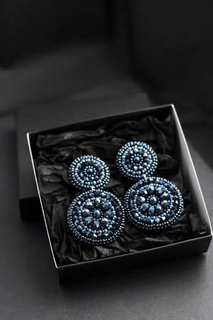 Deep blue seed beads embroidered statement earrings in a gift box on black background 版權商用圖片