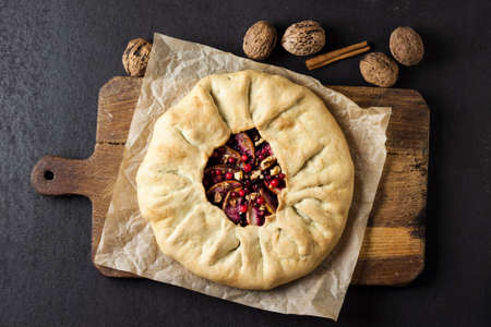 Homemade galette pie with apples, elder berries and walnuts decorated with fresh cowberry on rustic wooden board. Flat lay, top view 版權商用圖片