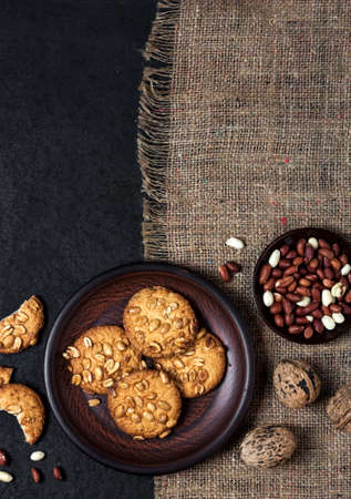 Homemade peanut cookies on a brown plate with raw peanuts in background. Rustic style food. Flat lay, top view, copy space 版權商用圖片