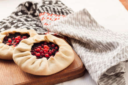 Homemade sweet galette with elderberries and cowberries on a wooden board 版權商用圖片