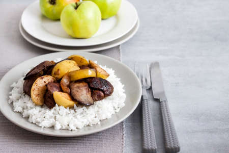 Fried chicken liver with apples served with white rice on a plate. Green apples on background. Copy space