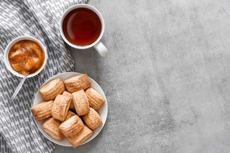 Tasty breakfast. Homemade sweet cinnamon cookies, cup of tea and apple confiture. Flatlay, top view, copy space