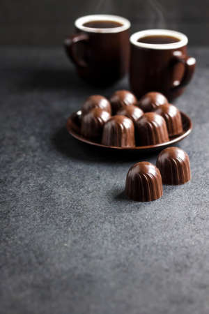 Chocolate candies on a plate and two cups of hot coffee on black background with copy space
