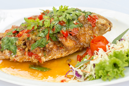 Deep fried red tilapia topped with sweet and sour sauce on top, Thai food.