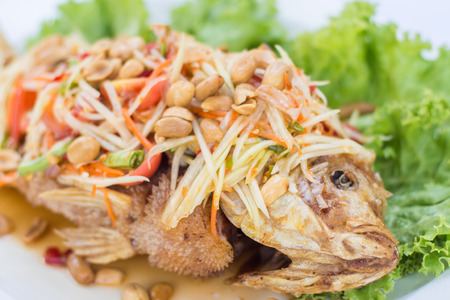 Deep fried red tilapia with papaya salad, Thai traditional food. Stock Photo
