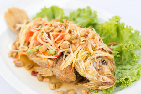 Deep fried red tilapia with papaya salad, Thai traditional food. Stock Photo