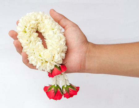 Hand holding a flower garland with jasmine & roses, Thai traditional culture.
