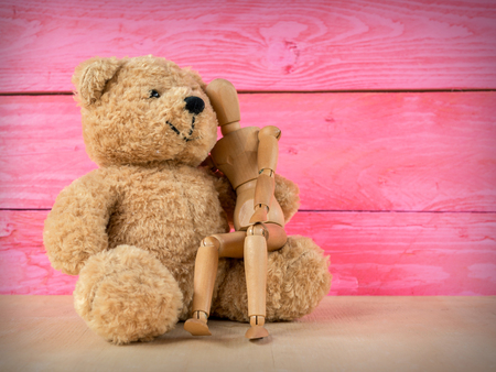 Wooden puppet with a teddy bear and a pink wooden background, together concept, template for design.