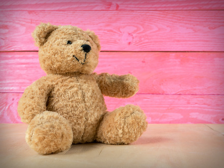 Teddy bear with pink wooden background, template for design. Stock Photo
