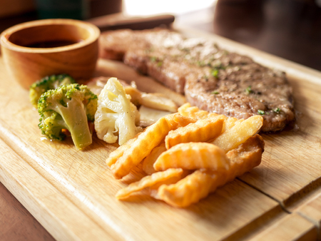 Delicious steaks with seasonings and herbs on wooden dish. Stock Photo