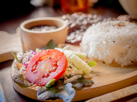 Rice, Delicious steaks with seasonings and herbs on wooden dish.