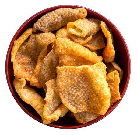 Crispy fried salmon skin in cup on white background.