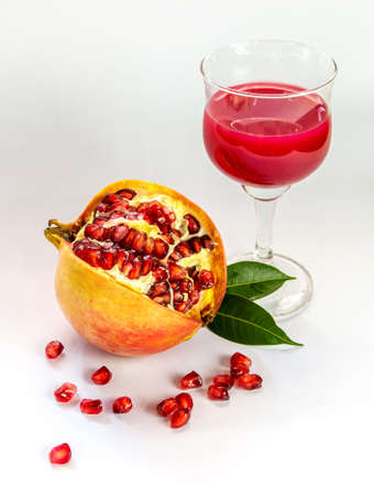 Ripe pomegranate with pomegranate juice in a glass on a white background. Standard-Bild