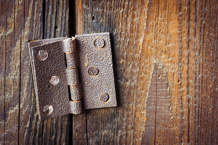 wicket gate: Old broken rusty hinge with bolts in it over a wooden background Stock Photo