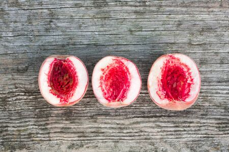 pit fall: Red peaches on a grey retro wooden background