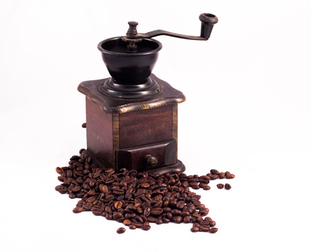 arabic coffee: Coffee mill, coffee grinder. Many coffee beans in the background. Texture of the coffee beans on a white background. Smelly, saturated brown arabic coffee beans Stock Photo