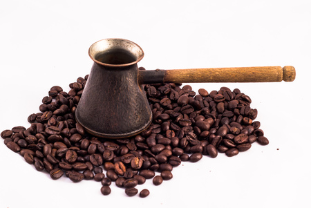 arabic coffee: Armenian Jazva, small pot for making coffee. Many coffee beans in the background. Texture of the coffee beans on a white background. Smelly, saturated brown arabic coffee beans Stock Photo