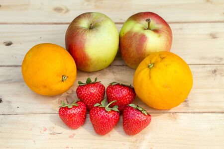 apples and oranges: Apples, oranges and strawberries on wooden table top view
