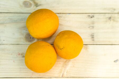 mellow: Fresh ripe oranges on wooden background. Exotic juicy mellow fruit