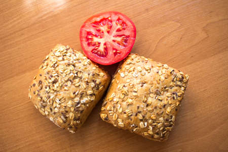 baton: Composition of whole grain bread buns and red fresh cut in half tomato on wooden table background Stock Photo