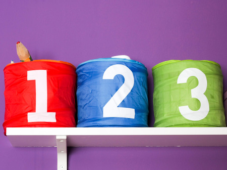 Colorful boxes for toys for children room on purple wall with numbers: One, Two, Three close up detail.