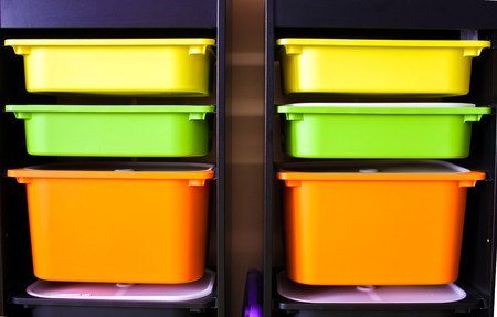 Two rows of Yellow, green and orange plastic boxes in black shelf Banque d'images
