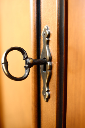Old vintage classic Metallic key in keyhole to open lock Stock Photo