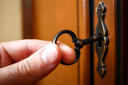Fingers of man inserting metallic key in keyhole to open lock