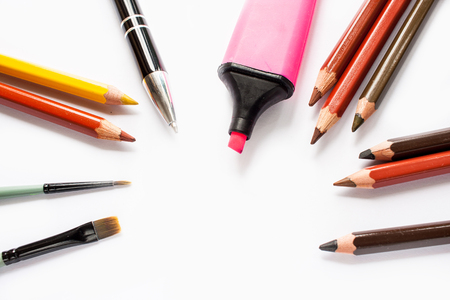 Lots of colorful pencils, purple pen marker, pen and brushes on white background Stock Photo