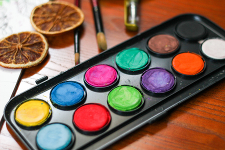 Artistic composition of black palette of paints, brushes, a painting on a paper, dried oranges and a little bird on wooden background. Painting or drawing set Stock Photo