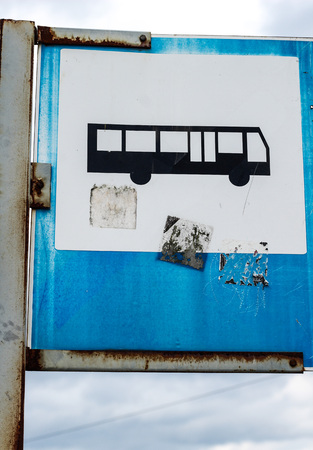 dirty car: Old wretched grungy bus sign on blue sky with clouds