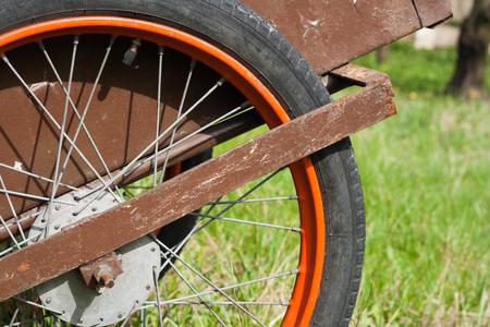 Wheelbarrow wheel close up on green grass back ground