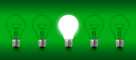 Row of a 5 light bulbs photograph on a green background isolated