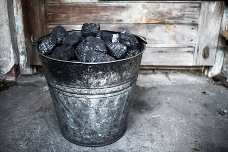 Black coal, carbon in old grungy metallic bucket
