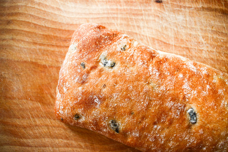 Bread bunn with olives on wooden board on wooden background close up focus