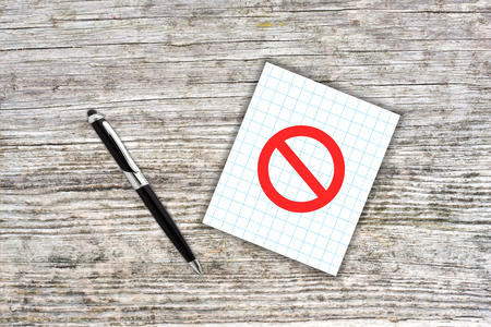 to restrain: Red prohibition symbol on checkered paper note with pen. Wooden background. Censorship concept