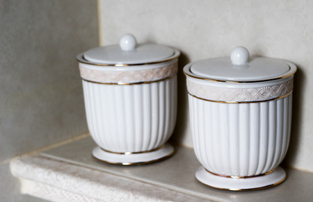 Two white decorative porcelain cups or containers with lids. Stylish baroque design art on white marble drawer Stock Photo
