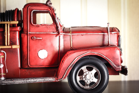 Car plastic model of an old classic red Fire Truck on a stripped wallpaper close up detail. Toy for a boy