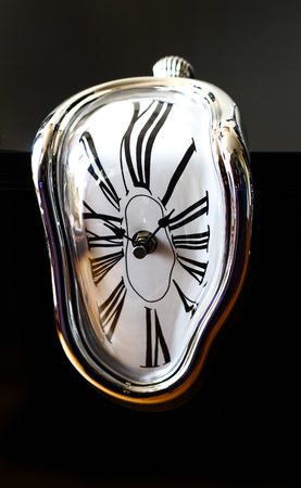 Distorted photograph of a surreal watch over black background. Detail