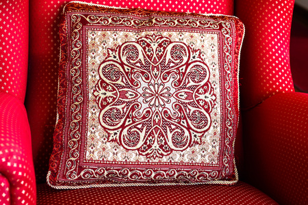 Red pattern cushion pillow on red chair in the room of the hose. Cozy home, composition inside. Close up, detail