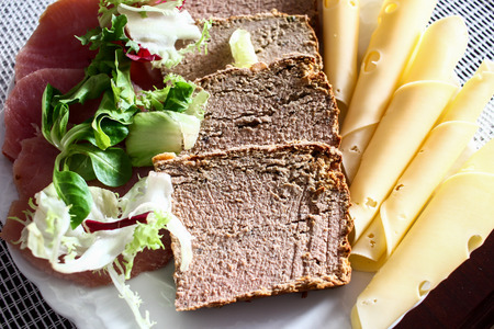Composition of food appetizers: pate, yellow cheese slices, green fresh lettuce and ham on plate on table in the morning for breakfast after a holiday