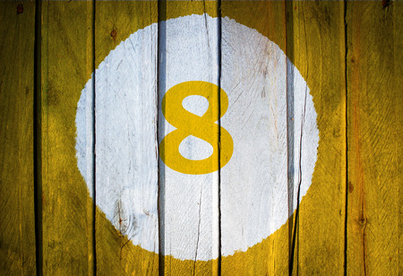 House number or calendar date in white circle on yellow toned wooden door background. Number eight 8