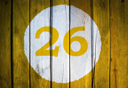 House number or calendar date in white circle on yellow toned wooden door background. Number 26 twenty six