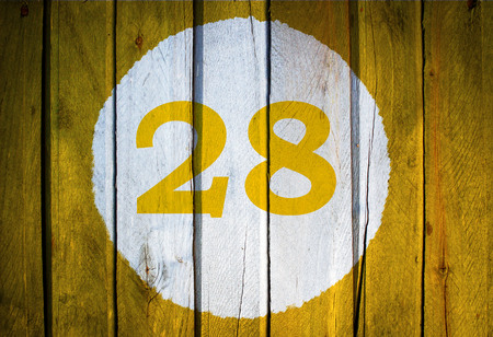 storehouse: House number or calendar date in white circle on yellow toned wooden door background. Number twenty eight 28